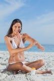 Femme heureuse s'asseyant sur la plage appliquant la protection solaire photographie stock libre de droits