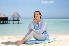 Femme heureuse s'asseyant sur la plage d'été images libres de droits