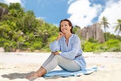 Femme heureuse s'asseyant sur la plage d'été sur les Seychelles image libre de droits