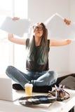 Femme heureuse s'asseyant sur la table et célébrant le succès Images libres de droits