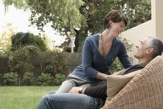 Femme heureuse s'asseyant sur Lap In Lawn de l'homme image stock