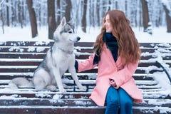 Femme heureuse s'asseyant sur le banc avec le chien de traîneau Photo stock
