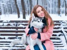 Femme heureuse s'asseyant sur le banc avec le chien de traîneau Images stock