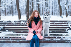 Femme heureuse s'asseyant sur le banc avec le chien de traîneau Images libres de droits