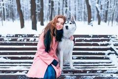 Femme heureuse s'asseyant sur le banc avec le chien de traîneau Photos stock