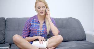 Femme heureuse s'asseyant sur le divan appelant par le téléphone clips vidéos
