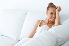 Femme heureuse s'asseyant sur le divan dans sa maison Photographie stock libre de droits