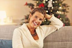 Femme heureuse s'asseyant sur le sofa au-dessus des décorations de Noël Image libre de droits