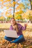 Femme heureuse s'asseyant sur les feuilles sèches avec l'ordinateur portable photos stock