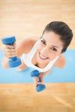 Femme heureuse s'exerçant avec des haltères sur le smili bleu de tapis d'exercice Image libre de droits