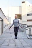 Femme heureuse s'exerçant avec la saut-corde dehors Images stock