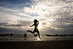 Femme heureuse sautant dans le coucher du soleil de mer Photo libre de droits