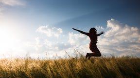 Femme heureuse sautant dans le pré Image libre de droits
