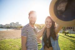 Femme heureuse se tenant avec l'ami en dehors de tenir le chapeau Photo libre de droits