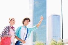 Femme heureuse se tenant avec l'ami masculin grêlant un taxi dans la ville Image libre de droits