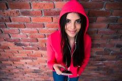 Femme heureuse se tenant avec le smartphone Images libres de droits