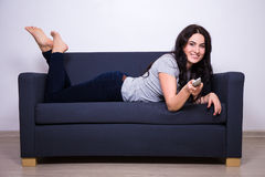 Femme heureuse se trouvant au sofa et à la TV de observation à la maison Photos libres de droits