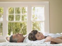 Femme heureuse se trouvant avec le mari dans le lit image libre de droits