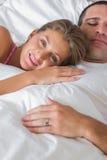 Femme heureuse se trouvant sur le coffre de maris dans le lit Photos libres de droits