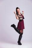 Femme heureuse soulevant une jambe dans le ciel Photographie stock libre de droits