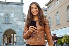 Femme heureuse souriant et marchant dans la rue utilisant un nouvel APP sur le smartphone photographie stock