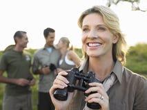 Femme heureuse tenant des jumelles avec des amis à l'arrière-plan Images libres de droits