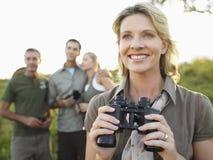 Femme heureuse tenant des jumelles avec des amis à l'arrière-plan Photos stock