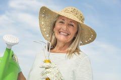 Femme heureuse tenant l'équipement de jardinage contre le ciel Image libre de droits