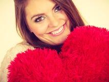 Femme heureuse tenant l'oreiller en forme de coeur Image stock