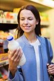 Femme heureuse tenant la bouteille à lait sur le marché Photographie stock