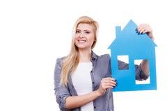 Femme heureuse tenant la maison de papier bleu Image libre de droits