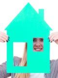 Femme heureuse tenant la maison de papier bleu Photographie stock libre de droits