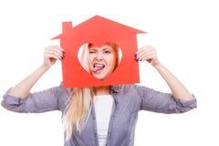 Femme heureuse tenant la maison de papier rouge image stock