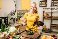 Femme heureuse tenant la salade, faisant cuire la nourriture saine images stock