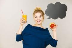 Femme heureuse tenant le jus d'orange frais photos stock