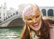 Femme heureuse tenant le masque de Venise dans l'avant du pont de Rialto Photo stock