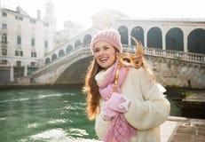 Femme heureuse tenant le masque de Venise dans l'avant du pont de Rialto Images stock