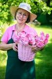 Femme heureuse tenant le panier des roses dans le jardin Images stock
