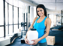 Femme heureuse tenant le récipient en plastique avec la nutrition de sports Photos stock