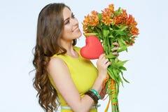 Femme heureuse tenant le symbole du coeur d'amour et des fleurs jaunes Photographie stock libre de droits