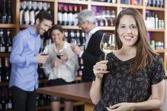 Femme heureuse tenant le verre à vin avec des amis à l'arrière-plan Photo libre de droits