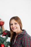 Femme heureuse tenant une boule de l'arbre de Noël Photo libre de droits