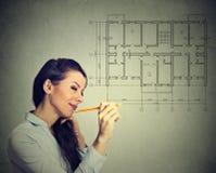 Femme heureuse traçant le plan d'étage de nouvelle maison avec le crayon Photo libre de droits