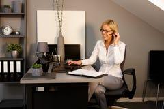 Femme heureuse travaillant dans le bureau photos stock