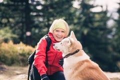 Femme heureuse trimardant et marchant avec le chien dans la forêt d'automne, ami Photo libre de droits