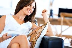 Femme heureux affichant un livre se reposant sur un sofa photo stock