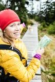 Femme heureux augmentant et affichant la carte dans la forêt Photo libre de droits