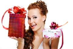 Femme heureux choisissant entre deux présents Photographie stock libre de droits