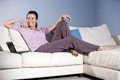 Femme heureux détendant sur le divan souriant avec l'ordinateur portatif images stock