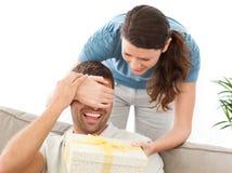 Femme heureux donnant un présent à son mari Photos stock